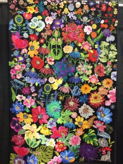"""""""The Spirit of Summer"""" by Susan Walen from Bethesda, MD. Machine appliqued, machine quilted, original design. Susan writes: In the dead of winter, I had a total knee replacement. I spend many hours in my armchair, happily cutting flowers out of my large stash of floral fabrics. Visitors did too. Ordered a large piece of industrial black felt, and played with many arrangements of flowers from my basket. I submit what I feel was my best arrangement of colors, shapes, and negative spaces. Free-motion quilting holds it together. I snuck in a few little surprises for the viewer."""