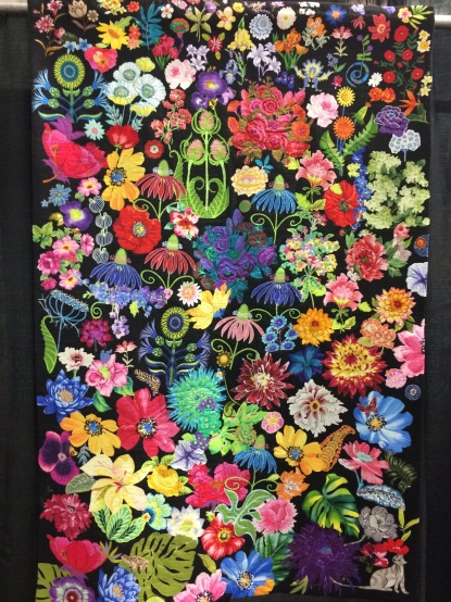 """The Spirit of Summer"" by Susan Walen from Bethesda, MD. Machine appliqued, machine quilted, original design. Susan writes: In the dead of winter, I had a total knee replacement. I spend many hours in my armchair, happily cutting flowers out of my large stash of floral fabrics. Visitors did too. Ordered a large piece of industrial black felt, and played with many arrangements of flowers from my basket. I submit what I feel was my best arrangement of colors, shapes, and negative spaces. Free-motion quilting holds it together. I snuck in a few little surprises for the viewer."