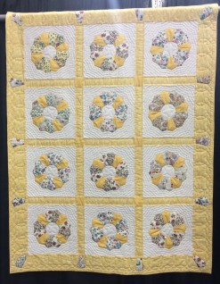 """Great Grandmas Plates"" by Elise Bowers from Harleysville, PA. Hand appliqued, machine pieced, hand quilted, original design. Elise writes: My great grandmother was a quilter, the last one in the family until I came along. Among the scraps I received from her estate were 11 finished Dresden plates plus pieces to finish many more. I completed a twelfth plate can you tell which one?) and made this small quilt in her memory. The quilt ""star"" in the center of each plate was hers, the template handmade from a piece of scrap cardboard. Since she often employed echo quilting, I decided to quilt in that fashion as well. She was a persnickity quilter: my father an aunt love to tell the story of her pulling out other ladies stitches when she returned home from the quilting bee. I'd like to believe her spirit guides my own hands as I quilt, proudly carrying on her legacy."
