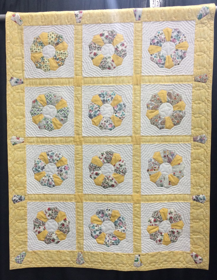 """""""Great Grandmas Plates"""" by Elise Bowers from Harleysville, PA. Hand appliqued, machine pieced, hand quilted, original design. Elise writes: My great grandmother was a quilter, the last one in the family until I came along. Among the scraps I received from her estate were 11 finished Dresden plates plus pieces to finish many more. I completed a twelfth plate can you tell which one?) and made this small quilt in her memory. The quilt """"star"""" in the center of each plate was hers, the template handmade from a piece of scrap cardboard. Since she often employed echo quilting, I decided to quilt in that fashion as well. She was a persnickity quilter: my father an aunt love to tell the story of her pulling out other ladies stitches when she returned home from the quilting bee. I'd like to believe her spirit guides my own hands as I quilt, proudly carrying on her legacy."""