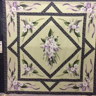 "World Quilt Competition XVII: Best of Country, New Zealand - ""Arum Bouquets"" by Anne Yeo. Hand appliqued, machine pieced, machine quilted. Anne writes: My original inspiration was a bouquet of lilies in a church. This formed the bouquet in the central diamond. The 8 other bouquets were designed to fit the 8 corners formed by the squares and diamonds of the quilt layout. Techniques used are hand needleturn applique, machined embroidery, domestic machine quilted, hand couched fine gold cord around the ribbons. I feel that this design and quilt layout work very well together."