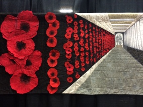 "World Quilt Competition XVII: Honorable Mention - ""Soldier On"" by Lucy Carroll from Australia. Hand appliqued, machine appliqued, machine pieced, machine quilted, original design. Lucy writes: Soldier On is my interpretation of the Roll of Honour at the Australian War Memorial. The placing of poppy is a poignant act which connects us with fallen soldiers through the generations. When we visit the Memorial I take my children to place their own poppies beside the names of my friends and former classmates lost in recent conflicts."
