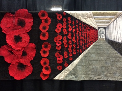 """World Quilt Competition XVII: Honorable Mention - """"Soldier On"""" by Lucy Carroll from Australia. Hand appliqued, machine appliqued, machine pieced, machine quilted, original design. Lucy writes: Soldier On is my interpretation of the Roll of Honour at the Australian War Memorial. The placing of poppy is a poignant act which connects us with fallen soldiers through the generations. When we visit the Memorial I take my children to place their own poppies beside the names of my friends and former classmates lost in recent conflicts."""