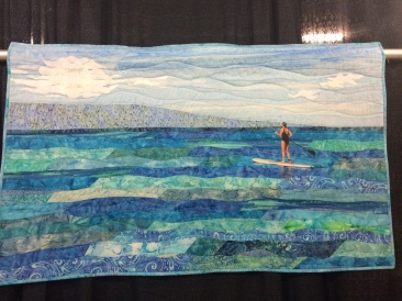 """""""Peaceful Paddling"""" by Babette Galinak from Flemington, NJ. Hand appliqued, machine pieced, machine quilted, original design. Babette writes: The spirit of nature influences my quilting. Immersing myself in our beautiful natural world as often as possible through hiking, kayaking, SUPing, etc. provides quiet time to dream about new quilting projects and allow the natural world to influence my work. The inspiration for Peaceful Paddling came from a perfect afternoon of paddling in Maui. Organic shapes, tropical batiks, a little glitter and a """"hidden"""" quilt block merge the spirit of nature and quilting."""